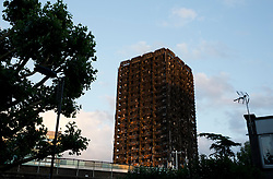 © Licensed to London News Pictures. 12/07/2017. LONDON, UK. A view of Grenfell Tower, west London, seen on Wednesday 12 July, 2017. Residents held a vigil this evening at the memorial wall by Latimer Station, west London, to remember those killed in the Grenfell Tower fire four weeks on from the tragedy when around 80 people are thought to have been killed. Photo credit: ISABEL INFANTES/LNP