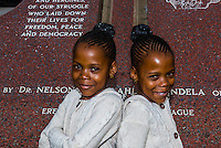 Twins stand in front of the Hector Pieterson Memorial, Soweto, Johannesburg, South Africa.
