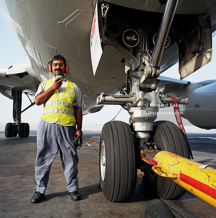 A Bahrani aircraft mechanic stands beneath the giant nose wheel assembly of a Being airliner at Bahrain International Airport. Wearing a red headset, he can communicate by cable with the pilots high up in the aircraft's cockpit as a vehicle pushes-back the flying machine onto the taxi-way before starting its engines and departure. It is another hot day in this Gulf State, a key hub airport in the region, providing a gateway to the Northern Gulf. The airport is the major hub for Gulf Air which provides 52% of overall movements. It is also the half-way point between Western Europe and Asian destinations such as Hong Kong and Beijing. Picture from the 'Plane Pictures' project, a celebration of aviation aesthetics and flying culture, 100 years after the Wright brothers first 12 seconds/120 feet powered flight at Kitty Hawk,1903. .