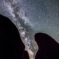 The Milky Way as seen in a gap between two granite boulders in the Sierra Nevada mountains of California.