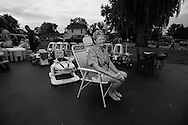 """Village of Cayuga resident Sandy Ehrlich sits in her driveway for a portrait among childrens toys during the annual """"50 Mile Yardsale"""", Saturday, July 20, 2016 along Route 90 in the Cayuga Lake region of the Finger Lakes, New York."""