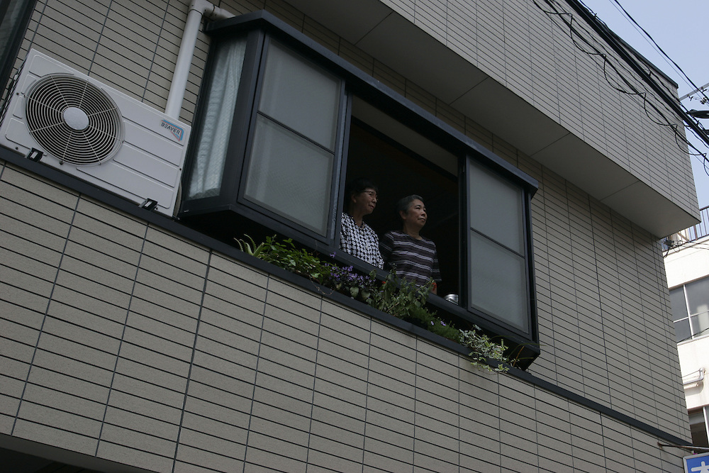 Emi Taniguchi at the  home of  her  sister and the  location of  her family  house which was burned in the  fire following the  explosion. pictured in the  window alone and with her  Sister ..Kinoshita - who was 15