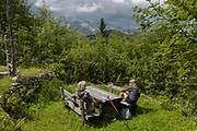 Walkers rest at a picnic table that overlooks the jighest of Slovenian mountains of Triglav national Park, in Velika Planina, on 26th June 2018, in Velika Planina, near Kamnik, Slovenia. Velika Planina is a mountain plateau in the Kamnik–Savinja Alps - a 5.8 square kilometres area 1,500 metres (4,900 feet) above sea level. Otherwise known as The Big Pasture Plateau, Velika Planina is a winter skiing destination and hiking route in summer. The herders' huts became popular in the early 1930s as holiday cabins (known as bajtarstvo) but these were were destroyed by the Germans during WW2 and rebuilt right afterwards by Vlasto Kopac in the summer of 1945.
