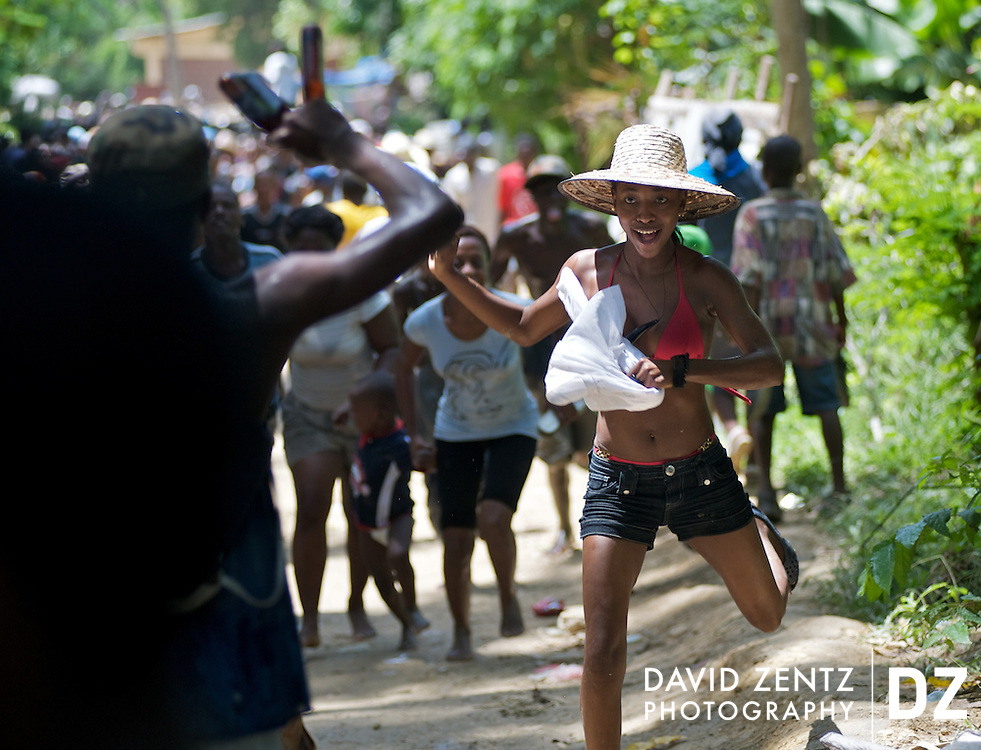 A pilgrim runs down a road in Ville Bonheur, Haiti, while making her way with others to the Saut D'eau waterfalls, the site of an annual voodoo pilgrimage on July 16, 2008. The 3-day festival turns the small village into a small city as thousands come from around the country and abroad to worship at the falls.