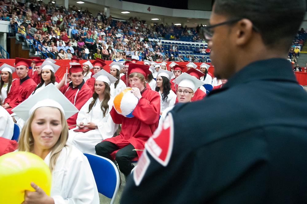 Lathan Goumas | MLive.com..A graduate blows up a beach ball and watches a a security guard approaches during the 2012 Swartz Creek High School commencement ceremony at the Perani Arena in Flint, Mich. on Tuesday June 12, 2012.
