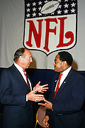 NFL Commissioner Pete Rozelle (left) has a discussion with an unidentified executive under an NFL shield banner during the 1987 NFL Draft on April 28, 1987 in New York, N.Y. (©Paul Anthony Spinelli)