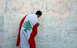 A Lebanese man writes on the wall outside of Prime Minister Rafik Hariri's grave, Beirut, Lebanon, Feb. 21, 2005. Several thousand Lebanese gathered at the scene of the bombing that killed Hariri. The crowd demanded a Syrian pullout and an international probe into the assassination.