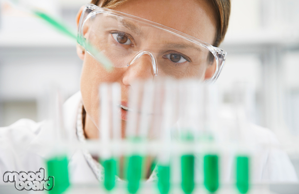 Scientist filling test tubes with pipette in laboratory close-up