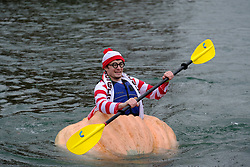 A man dressed as Waldo races a giant pumpkin across Lake of the Commons at the 14th annual West Coast Giant Pumpkin Regatta in Tualatin, Ore. on October 21, 2017. (Photo by Alex Milan Tracy)