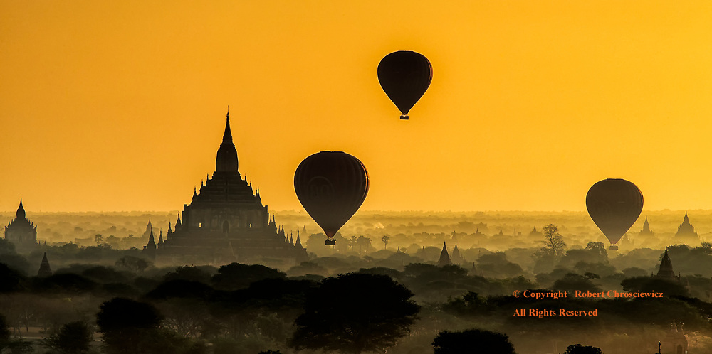 Balloon Silhouette: Balloons float over the ancient plains of Bagan, bathed in a yellow morning sky, over silhouettes of a ruined past, Bagan Myanmar.