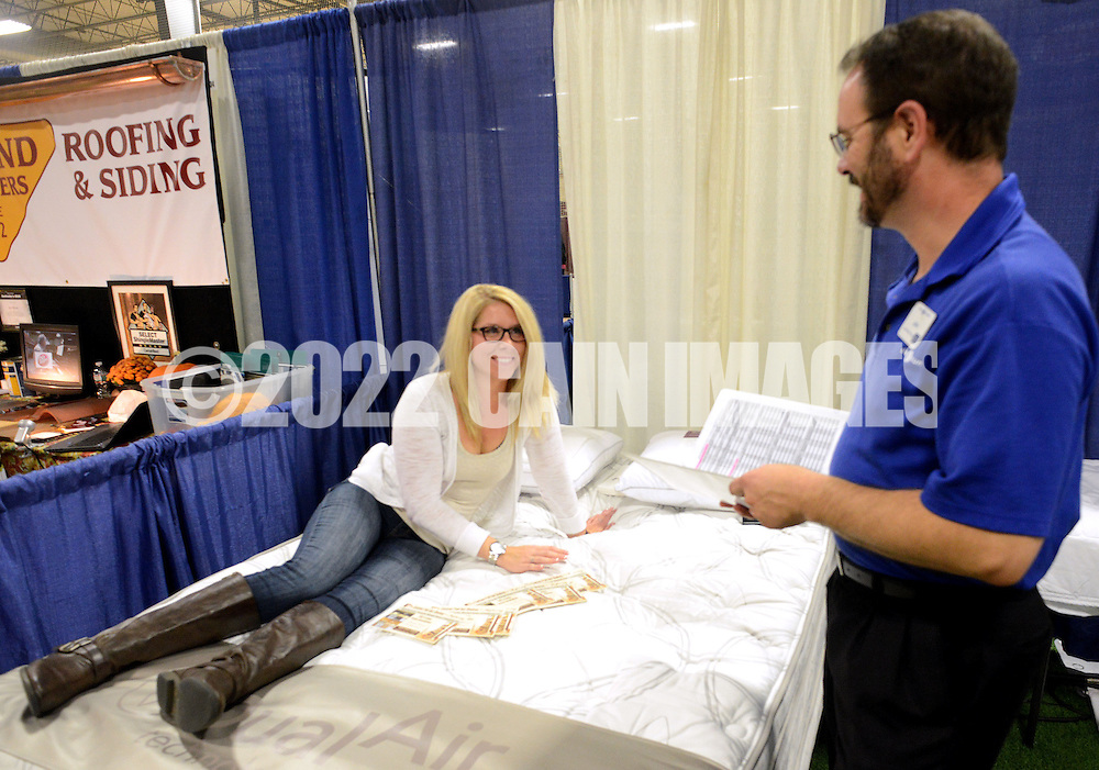 WARMINSTER, PA - OCTOBER 11: Samantha Borden, of Sewell, New Jersey lays on a mattress as she speaks with John McNamara of Sleep Number at the Bucks Montco Home at the Sportsplex October 11, 2014 in Warminster, Pennsylvania. (Photo by William Thomas Cain/Cain Images)