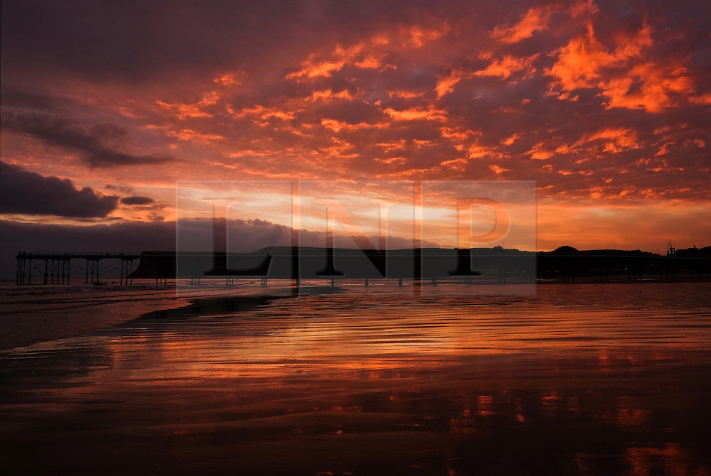 © Licensed to London News Pictures.11/10/15<br /> Saltburn, UK. <br /> <br /> A fiery Autumn sunrise lights up the clouds over the beach and pier at Saltburn by the Sea in Cleveland.<br /> <br /> Photo credit : Ian Forsyth/LNP