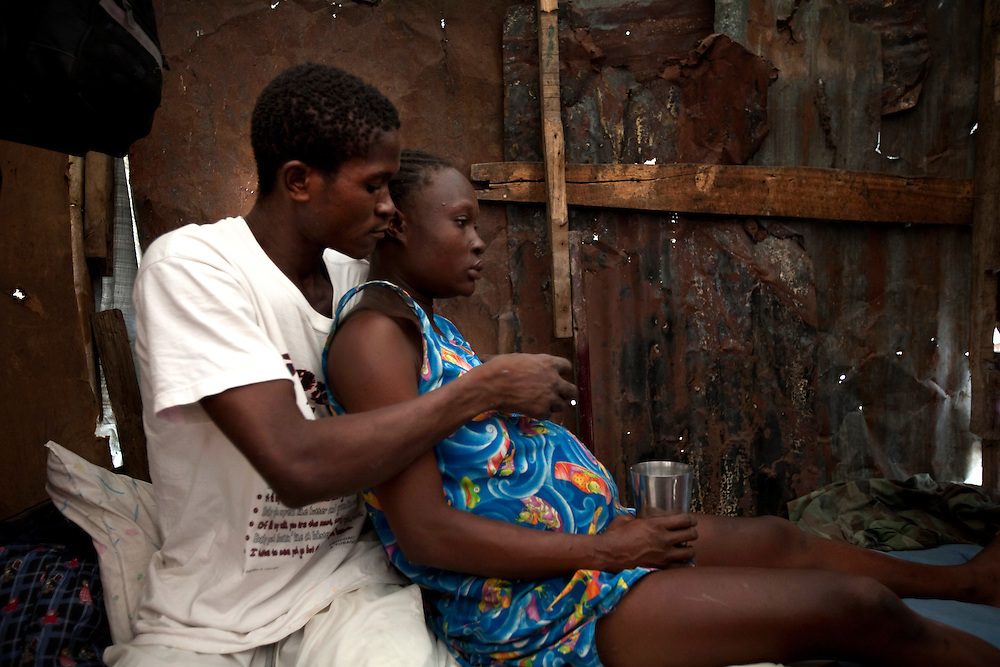 Boyfriend with Alexandra Pierie who is about to give birth to her son Nadav Di Grazia paul in the makeshift refugee camp, La Piste, in Port-au-Prince, Haiti on July 20, 2010. La Piste (French for &quot;runway&quot;)is a settlement sprawled across the site of a disused airport and now home to an estimated 20,000 earthquake survivors living in makeshift structures.<br /> Six month after a catastrophic earthquake measuring 7.3 on the Richter scale hit Haiti on January 13, 2010, killing an estimated 230,000 people, injuring an estimated 300,000 and making homeless an estimated 1,000,000.