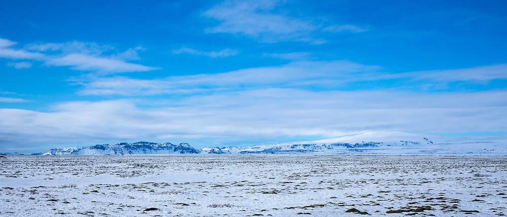 Spectacular typical Icelandic landscape blue sky over glaciers and snow-covered mountains in South Iceland