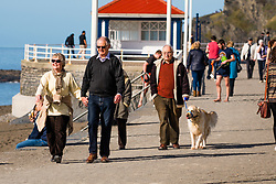 © Licensed to London News Pictures. 15/03/2017. Aberystwyth, Wales, UK. People enjoying walking in  the very warm spring afternoon  sunshine on the beach and promenade in Aberystwyth  on the Cardigan Bay coast of Ceredigion, West Wales. Photo credit: Keith Morris/LNP