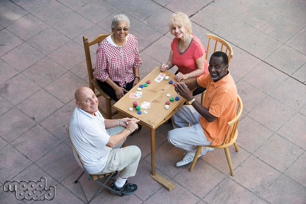 Senior people playing cards, smiling
