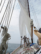 The Honorable Heather Somer, Mayor of Groton, Connecticut looks on as crew member Don Grinberg raises the sails aboard the tall ship schooner Tyrone during the Parade of Sail at OpSail Connecticut 2012. The Tyrone, captained by Matthew Sutphin, hails from Chatham Massachusetts.