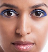 Close-up portrait of beautiful young woman with blue eyeshadow against white background