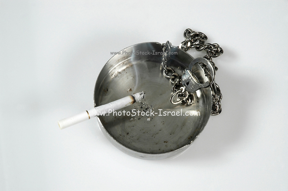 Cigarette, Ashtray and handcuffs A concept showing the addiction of people to cigarettes and  nicotine