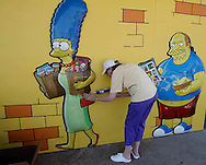 "Cutouts of ""The Simpsons"" character Marge Simpson is reaffixed to the wall by a worker in front of a 7-Eleven convenience store in Los Angeles, California, 03, July 2007 The store was converted into a ""Kwik-E- Mart"", made famous by the popular animated television program. Specially themed products from the show, such as cans of Buzz cola and Krusty-O's cereal, were on sale."