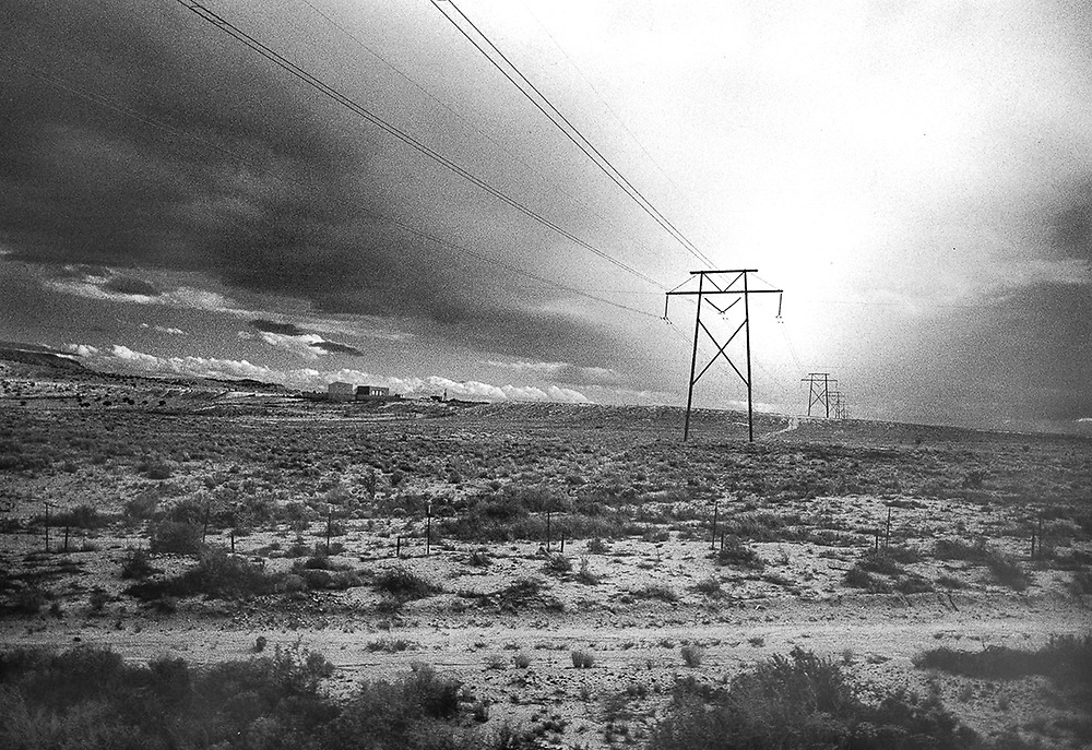 Black and white film image taken from a moving train, capturing the impact man makes across a desert landscape.