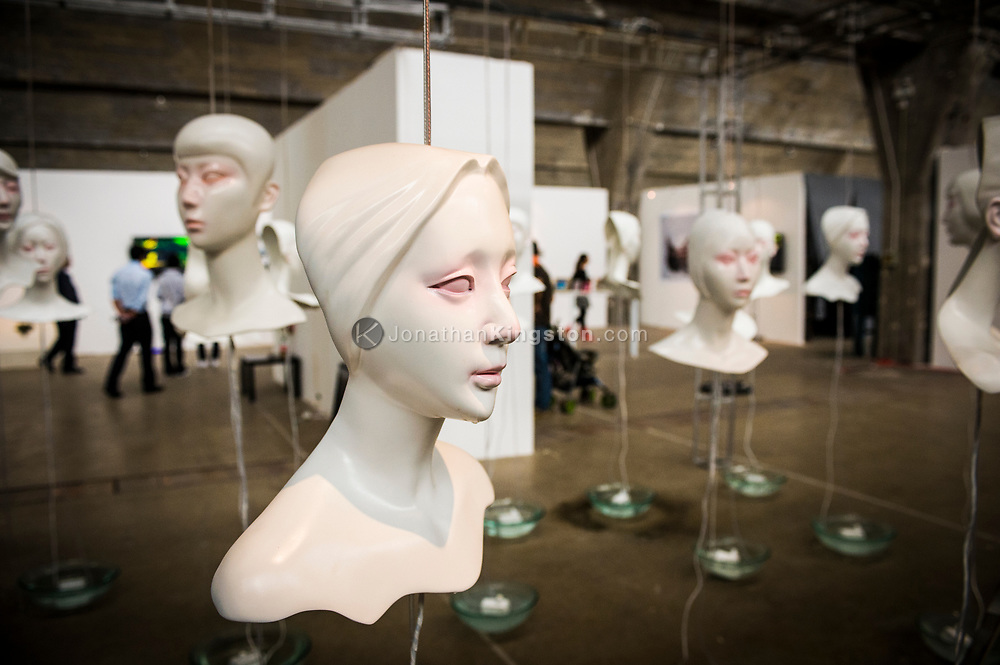 Suspended white sculpted heads in a gallery in the 798 Art Zone or Dashanzi Art District of Beijing, China.
