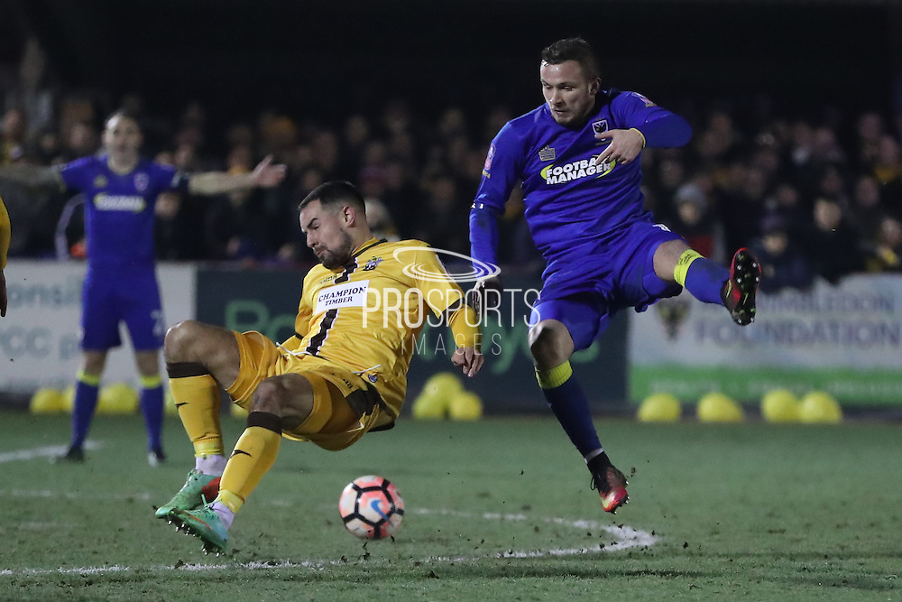 AFC Wimbledon midfielder Dean Parrett (18) and Sutton United Craig Eastmond (15) during the The FA Cup third round replay match between AFC Wimbledon and Sutton United at the Cherry Red Records Stadium, Kingston, England on 17 January 2017. Photo by Stuart Butcher.