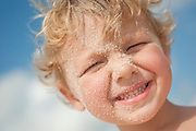Stock image for editorial and commercial usage of a boys sandy face on the beach.