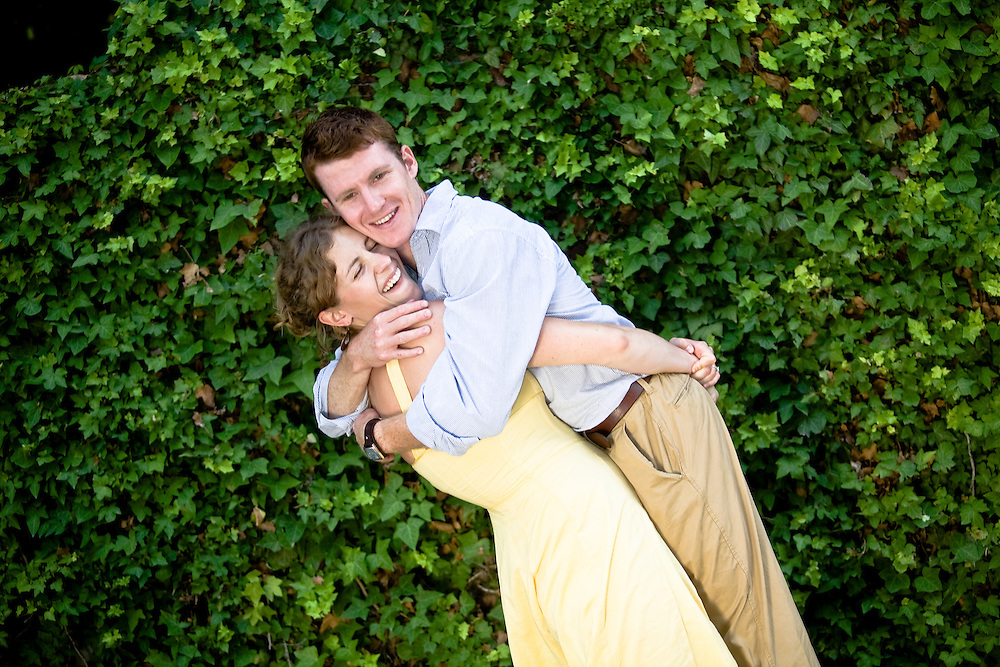 environmental portrait of engaged couple with ivy background.