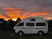 Orange rays of sunset brighten clouds over Peterborough, Victoria, Australia. Apollo campervan.