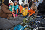 March 5, 2016 - Idomeni, Greece:  A family from Syria waits  near barbed wire at the  Idomeni border crossing in Greece. They  waited hours in the  hope to cross to Macedonia that day. 12,000 refugees are stuck here after Macedonia closed the border. New arrivals come in every day, making living conditions more and more difficult. (Steven Wassenaar/Polaris)