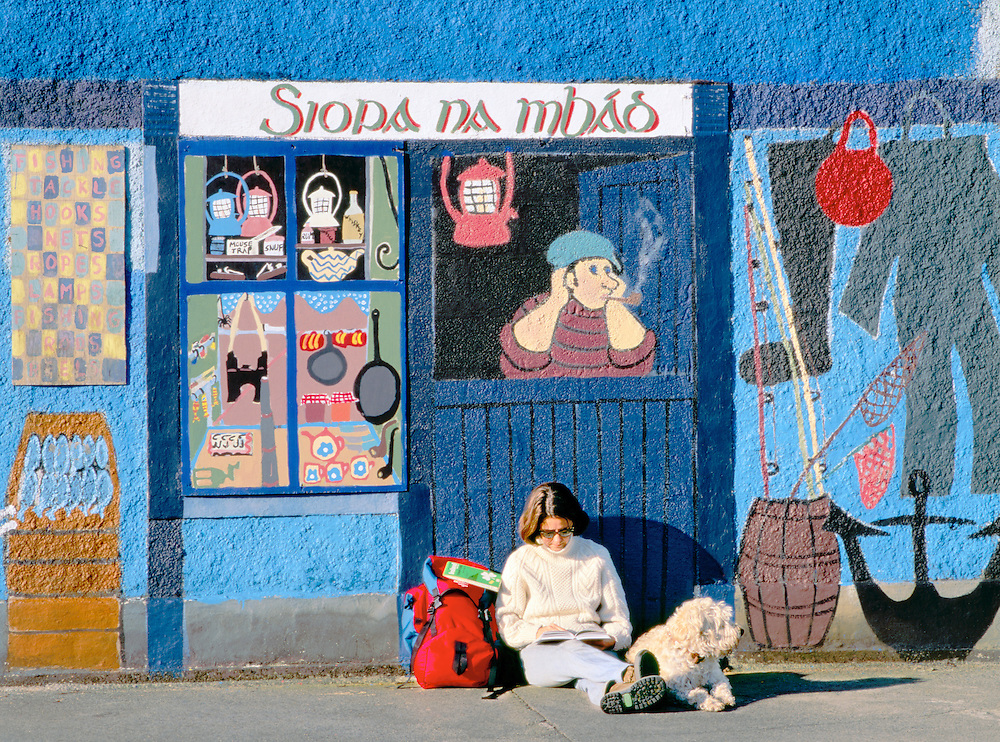 Kinvara village, Galway Bay, Ireland. Woman tourist reads guide book with dog in front of mural painting of fishing tackle shop.