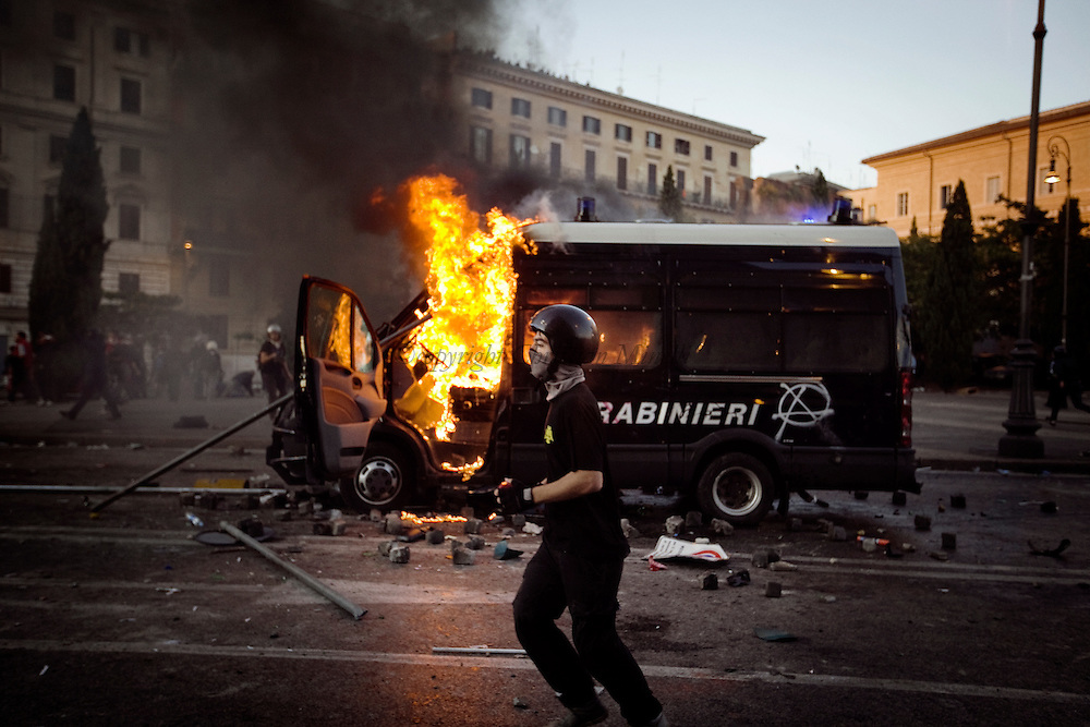 ITALY, Rome, October 15, 2011 : A protester runs by a Police van during a demonstration in Rome on October 15, 2011. © Christian Minelli/Emblema.