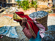02 MARCH 2017 - SANKHU, NEPAL: A laborer carries carry gravel to a home being rebuilt in Sankhu. Each basket weighs about 80 pounds. Almost all of the work is being done by hand. There is more construction and rebuilding going on in Sankhu, west of central Kathmandu, than in many other parts of the Kathmandu Valley nearly two years after the earthquake of 25 April 2015 that devastated Nepal. In some villages in the Kathmandu valley workers are working by hand to remove ruble and dig out destroyed buildings. About 9,000 people were killed and another 22,000 injured by the earthquake. The epicenter of the earthquake was east of the Gorka district.   PHOTO BY JACK KURTZ