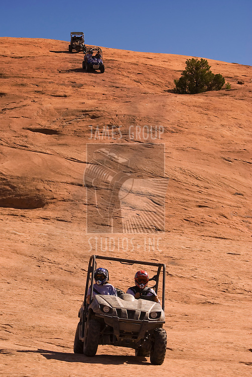3 side-by-side ATVs coming down the side of a rock decline.
