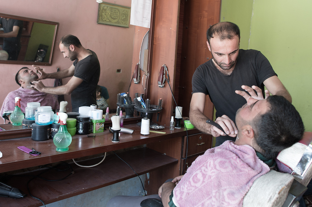The 29-year-old barber Bangin Muslim shaves a customer in his shop in Kobane. Although he has many customers, his income is not enough – because he is the only one in his family who has work. Kobanê (Ayn al-Arab), Syria, June 22, 2015