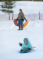 Ernie Boisvert watches as his granddaughter Autumn Boisvert takes a ride down the sledding hill at Gilford Outing Club Tuesday afternoon.  (Karen Bobotas/for the Laconia Daily Sun)