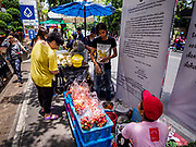 24 MARCH 2017 - BANGKOK, THAILAND: People walk past street food carts on Sukhumvit Soi 63 (Ekkamai) in the neighborhood carts are being evicted from. The sign in the background is the announcement that carts have to leave the neighborhood. Food cart vendors along Sukhumvit Road between Sois 55 (Thong Lo) and 69 (Phra Khanong) in Bangkok have been told by city officials that they have to leave the area by 17 April. It's a part of an effort by Bangkok city government, supported by the ruling junta, to take back the city's sidewalks. The evictions in the area are the latest in mass evictions of Bangkok street food vendors after similar actions elsewhere on Sukhumvit, in the Ari area, in Silom/Patpong and Ratchaprasong neighborhoods. The vendors in Thong Lo/Phra Khanong are popular with local office workers because most of the formal restaurants in the area serve foreign tourists and upper class Thais and are very expensive. The street food carts serve meals starting at about 35Baht ($1US). The city has not announced if they will provide alternative locations for the carts.     PHOTO BY JACK KURTZ
