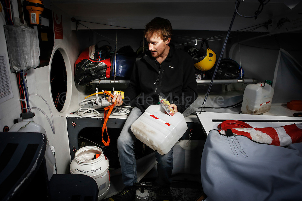New Zealand sailor Conrad Colman on his boat the day after he crossed the Vendee Globe Race finish line in Sables d'Olonne. Showing equipment from the emergency kit container from which he ate the last food rations. 25 February 2017.