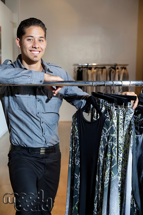Portrait of a happy young male standing by clothes rack in fashion store