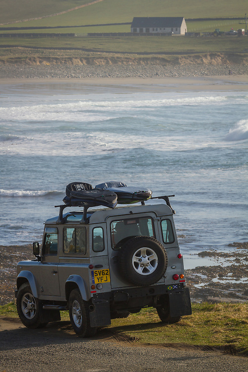 A tourist waits in a Land Rover over the Bay of Skaill, Orkney, Scotland
