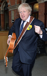 Boris Johnson tries his hand at guitar playing.<br /> Mayor of London Boris Johnson joins musicians at St Pancras Station to urge young musicians to take to the streets and continue busking in the Capital.  <br /> <br /> Wednesday, 9th April 2014. Picture by Ben Stevens / i-Images