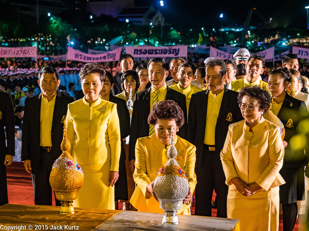 05 DECEMBER 2015 - BANGKOK, THAILAND:  Thai women make merit by presenting the King's representatives with gifts that represent lotus buds on the King's Birthday on Sanam Luang in Bangkok. Thais marked the 88th birthday of Bhumibol Adulyadej, the King of Thailand,  Saturday. The King was born on December 5, 1927, in Cambridge, Massachusetts. The family was in the United States because his father, Prince Mahidol, was studying Public Health at Harvard University. He has reigned since 1946 and is the world's currently the longest serving monarch in the world and the longest serving monarch in Thai history. Bhumibol, who is in poor health, is revered by the Thai people. His birthday is a national holiday and is also celebrated as Father's Day. He is currently hospitalized in Siriraj Hospital, recovering from a series of health setbacks.   PHOTO BY JACK KURTZ