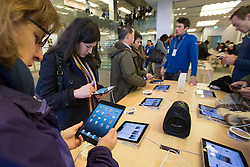 © licensed to London News Pictures. London, UK 02/11/2012. People looking at iPad Mini at Apple Store on Regent Street, London as highly anticipated tablet meets the costumers on 02/11/12. Photo credit: Tolga Akmen/LNP