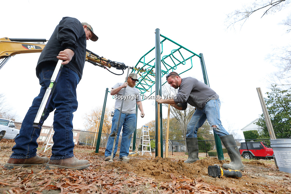 Thomas Wells | BUY AT PHOTOS.DJOURNAL.COM<br /> David Tidwell, left, and Jordon Hunt wait for Trey Permenter to remove excess dirt from the hole so they can level the new playground equipment they are installing at Milam Elementary School Wednesday afternoon.