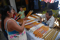 """MEXICO, Veracruz, Tantoyuca, Oct 27- Nov 4, 2009. A family buys altar candles with special decorations in Huejutla's main market. """"Xantolo,"""" the Nahuatl word for """"Santos,"""" or holy, marks a week-long period during which the whole Huasteca region of northern Veracruz state prepares for """"Dia de los Muertos,"""" the Day of the Dead. For children on the nights of October 31st and adults on November 1st, there is costumed dancing in the streets, and a carnival atmosphere, while Mexican families also honor the yearly return of the souls of their relatives at home and in the graveyards, with flower-bedecked altars and the foods their loved ones preferred in life. Photographs for HOY by Jay Dunn."""