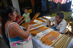 "MEXICO, Veracruz, Tantoyuca, Oct 27- Nov 4, 2009. A family buys altar candles with special decorations in Huejutla's main market. ""Xantolo,"" the Nahuatl word for ""Santos,"" or holy, marks a week-long period during which the whole Huasteca region of northern Veracruz state prepares for ""Dia de los Muertos,"" the Day of the Dead. For children on the nights of October 31st and adults on November 1st, there is costumed dancing in the streets, and a carnival atmosphere, while Mexican families also honor the yearly return of the souls of their relatives at home and in the graveyards, with flower-bedecked altars and the foods their loved ones preferred in life. Photographs for HOY by Jay Dunn."