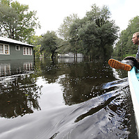 Darin Todd, 22, looks at homes on Happiness Lane in Colleton County as his grandfather navigates a motorboat Tuesday through the community inundated with more than 4 feet of floodwater from the Edisto River. (ANDREW KNAPP/STAFF)