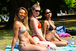 Friends Kyomi Cheyenne, 25, left, Ellisha Blake, 22, centre, and Chloe Gomez, 23, right soak up the sun beside The Serpentine in Hyde Park as temperatures soar beyond the mid-30s in London. London, July 25 2019.
