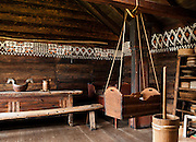 "The white chalk paint decoration on the wall is called ""kroting."" A baby cradle hangs from ropes. On the right is a butter churn made of wood. The Medieval room reconstructs Norwegian lifestyle from hundreds of years ago. The Hardanger Folk Museum was founded in 1911 in Utne, Norway."
